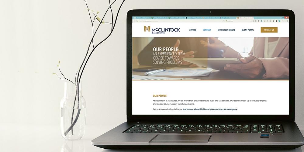 A laptop displaying the McClintock & Associates website.